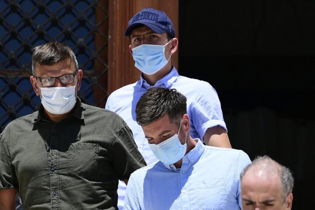 Гарри Магуайр (в синей кепке) покидает здание суда