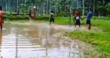 Нереальная бисеклета мальчишки из джунглей, которая сделана на поле с огромной лужей