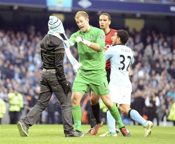 Вратарь Манчестер Сити защищает игрока МЮ от болельщика