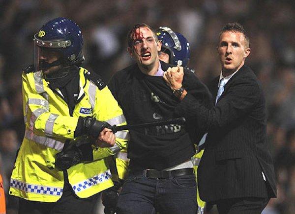 Полиция выводит одного из фанатов Миллуола с футбольного поля